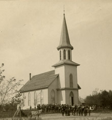 Sepia photo of church with crowd of people in front