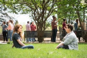 students sitting in the grass and talking