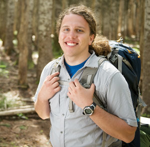 student backpacking in woods