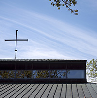 Church building with cross against blue sky