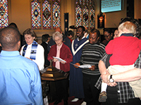 Hollie Holt-Woehl '93 M.Div., '08 Ph.D. (far left), leads a baptism service at Christ the River of Life Lutheran Church.