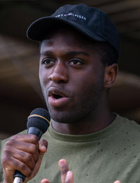 Black person speaking into a microphone